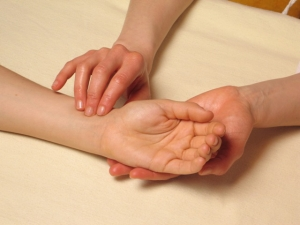 Acupuncturist taking the pulse of a patient